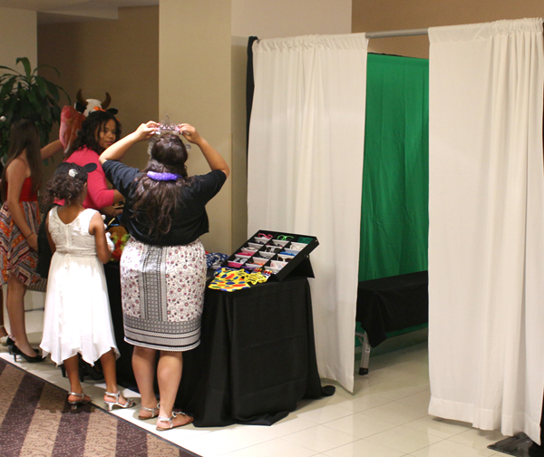 Green screen photo booth with white curtains.
